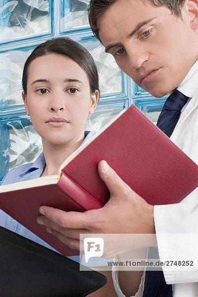 Männliche und weibliche Arzt diskutieren eine Medizinkartei