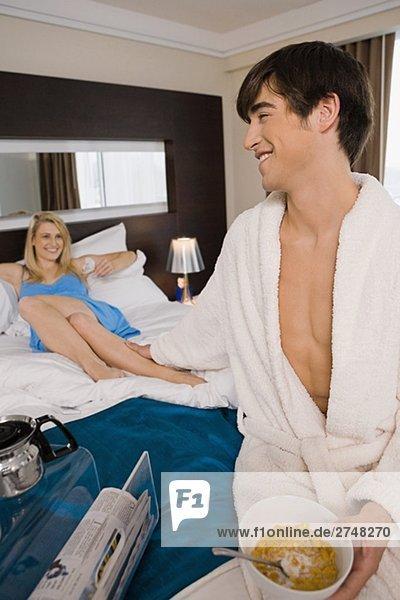 Junge Mann  der eine junge Frau Bein auf dem Bett hält