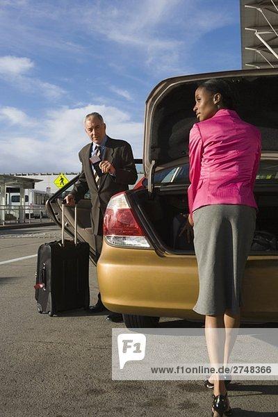 Geschäftsfrau entladen ihren Koffer aus einem Kofferraum mit einem Geschäftsmann vor ihr stehen