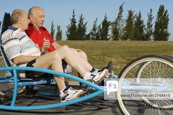 Zwei ältere Männer Reiten ein quadracycle