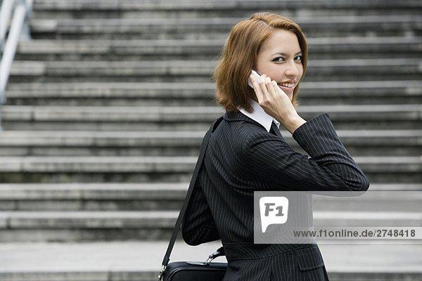 Porträt von geschäftsfrau Gespräch auf einem Mobiltelefon und lächelnd