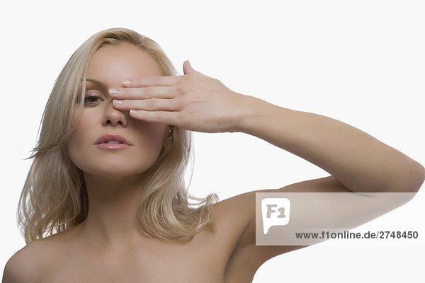 Nahaufnahme einer jungen Frau mit ihrem ein Auge mit der hand