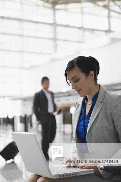 Geschäftsfrau sitzt auf einem Flughafen und benutze ein laptop