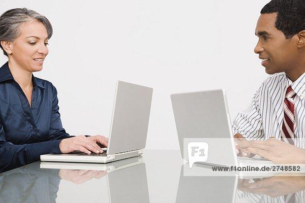 Geschäftsfrau und Geschäftsmann auf Laptops in einem Büro arbeiten
