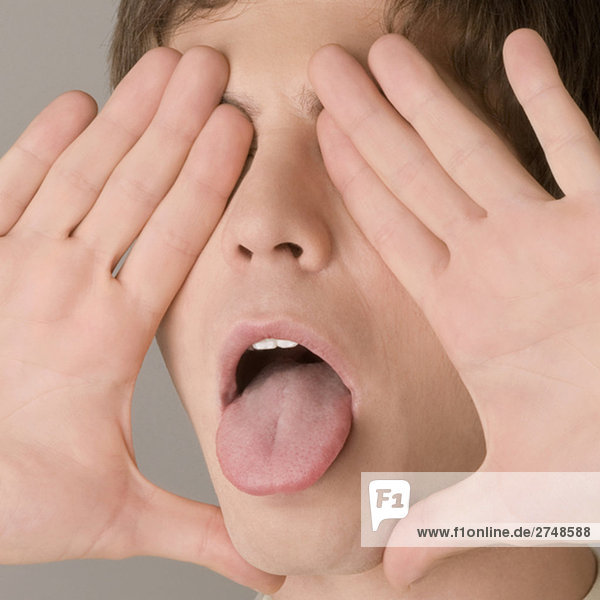 Nahaufnahme eines jungen Mannes  seine Zunge herausstrecken