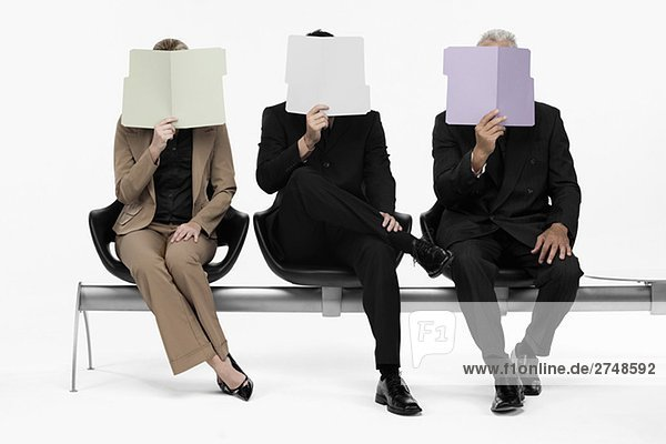 Two businessmen and a businesswoman holding files in front of their faces