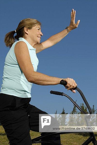 Seitenansicht ältere Frau Radfahren und winken ihre Hand