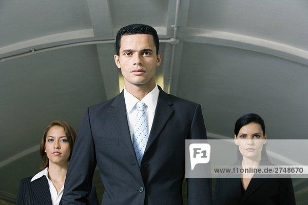Kaufmann stehend mit zwei Geschäftsfrauen in einer u-Bahnstation