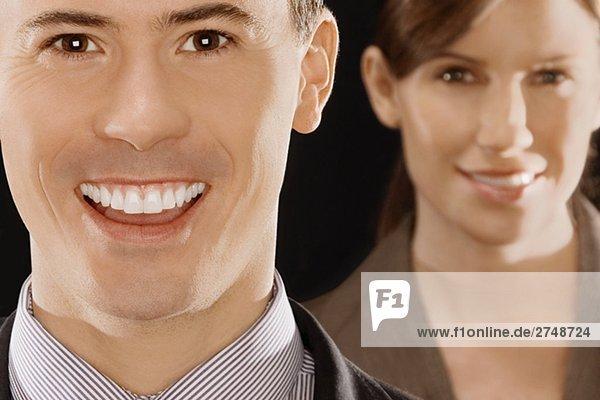 Porträt von einem Kaufmann lächelnd mit geschäftsfrau hinter ihr