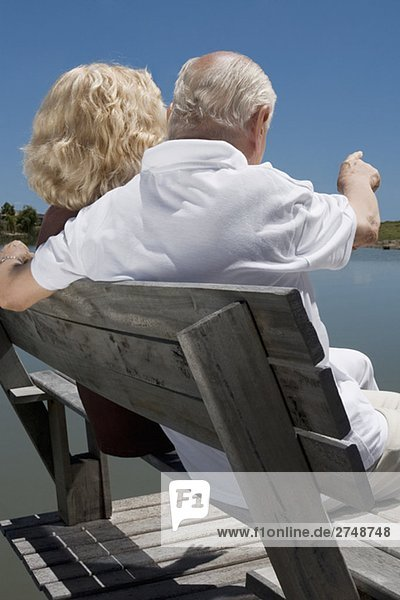 Rückansicht eines senior Paares sitzen auf einer Bank am Seeufer