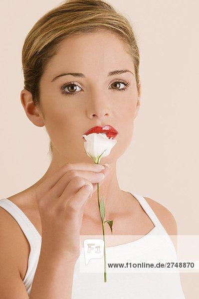 Portrait of a junge Frau hält eine Blume