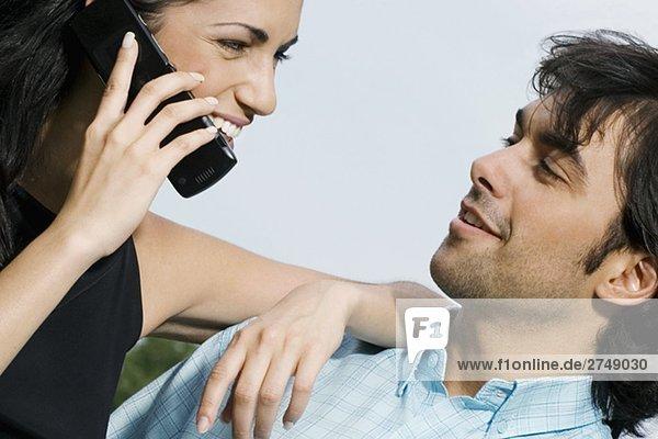 Nahaufnahme einer jungen Frau Gespräch auf einem Mobiltelefon und Blick auf einen jungen Mann