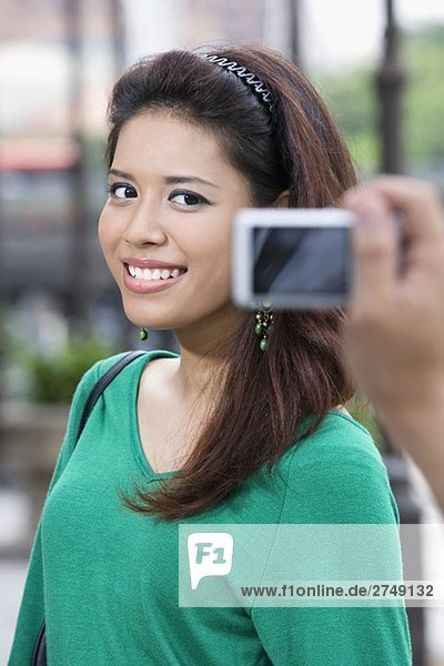 Close-up of a person's hand photographing of a young woman with a digital camera