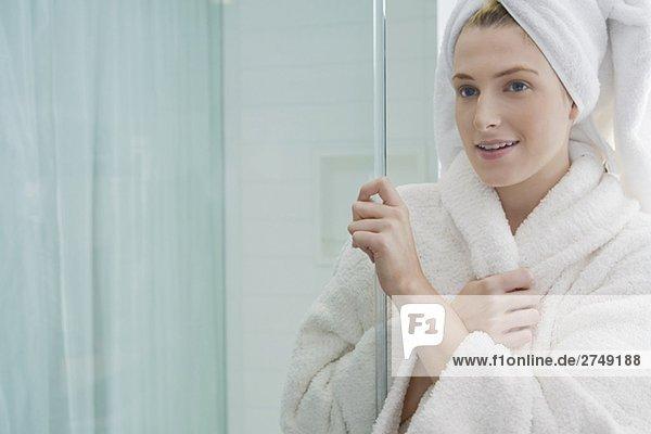 Nahaufnahme of a junge Frau hält eine Bildschirm-Tür und lächelnd