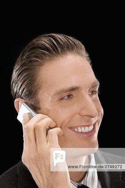 Nahaufnahme eines Kaufmanns auf einem Mobiltelefon reden und lächelnd