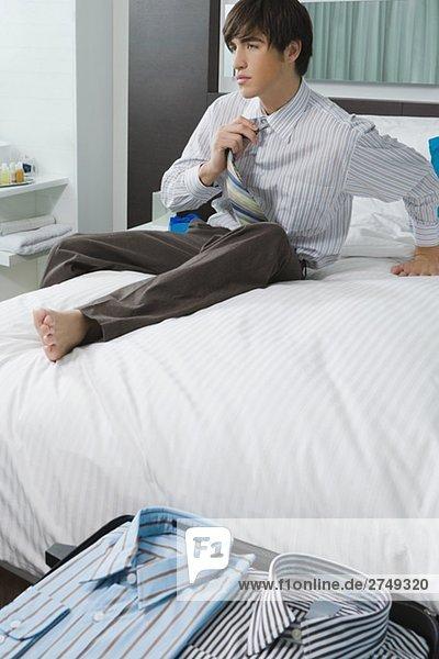 Kaufmann sitzen auf dem Bett und Aufhebung der Lieferbindungen Krawatte