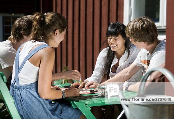 Zwei Mädchen und zwei Jungs spielen ein Spiel.
