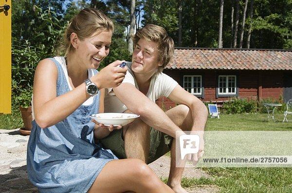 Mädchen und Kerl beim Frühstücken