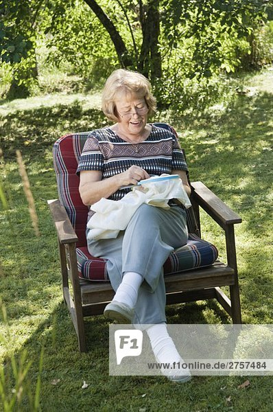 Woman in a chair sewing
