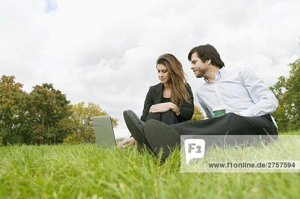 Frau und Mann auf dem Rasen sitzend mit Computer