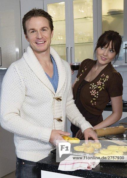 Mann und Frau beim Backen von Lucia-Brötchen