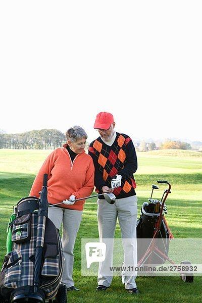 Ein älteres Ehepaar Golfen Skane Schweden.
