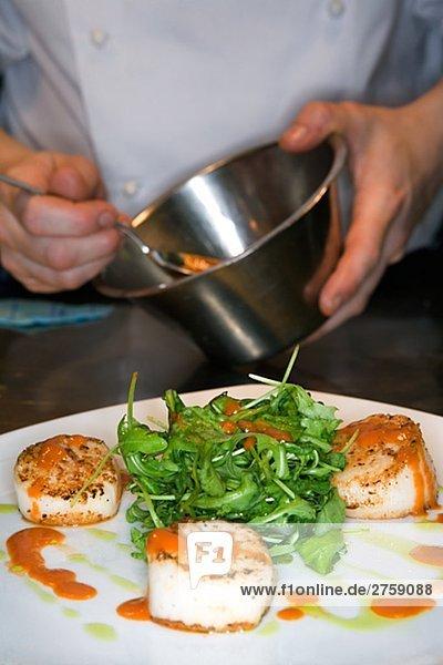 A cook preparing food in a restaurant kitchen Sweden.