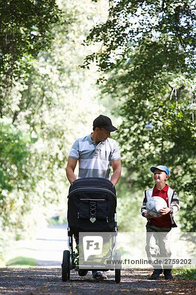 Vater und Sohn zu Fuß in einem Park am sonnigen Tag Schweden.