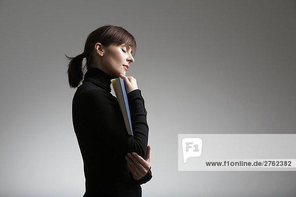 Seitenprofil of Frau hält Buch mit ihren Augen geschlossen, Seitenprofil of Frau hält Buch mit ihren Augen geschlossen
