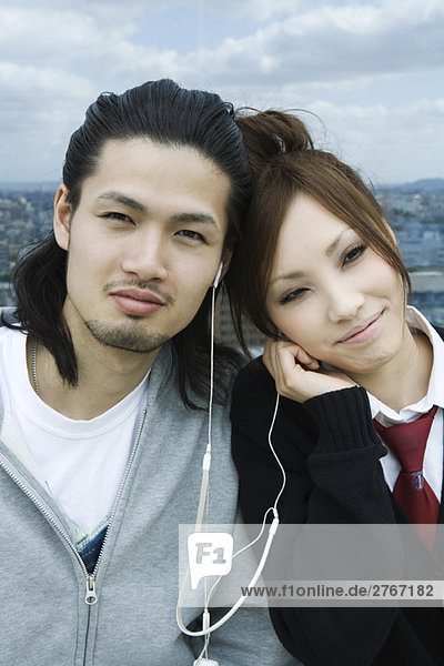 Young couple sharing earphones  smiling