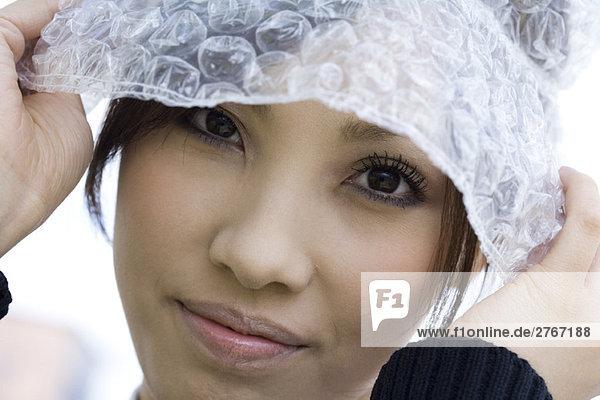 Female wearing hat made of bubble wrap  portrait