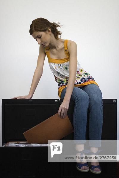 Frau sitzt auf den Aktenschränken und überprüft den Inhalt der Akte.