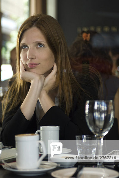 Frau im Café sitzend  träumend