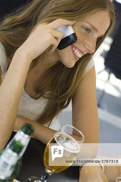 Junge Frau sitzt im Café im Freien  mit dem Handy