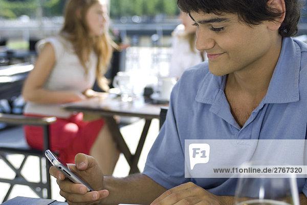 Junger Mann  der im Café im Freien sitzt und sein Handy benutzt.