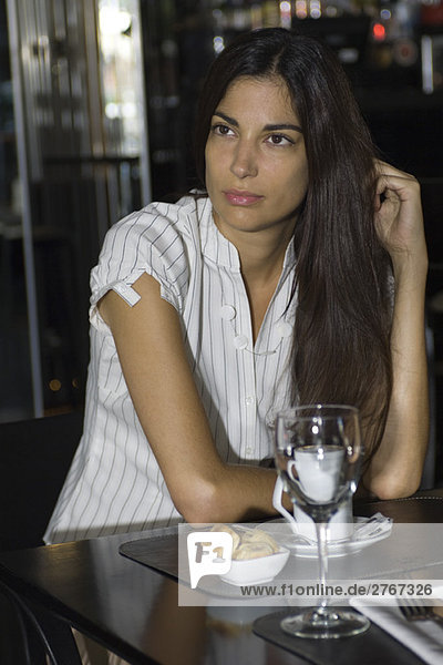 Brunette woman sitting in cafe  daydreaming