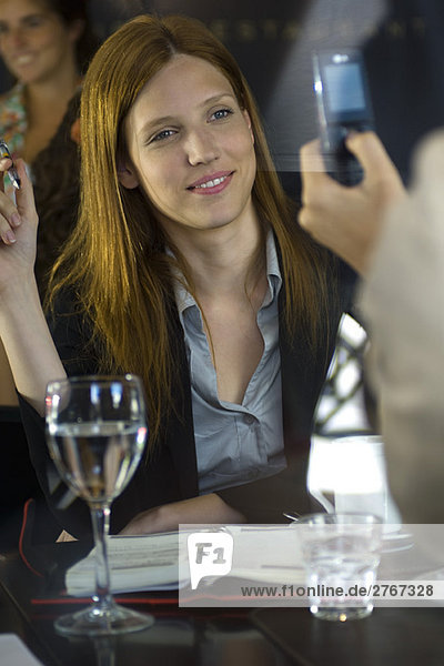 Frau posiert für ein Foto mit dem Handy im Café