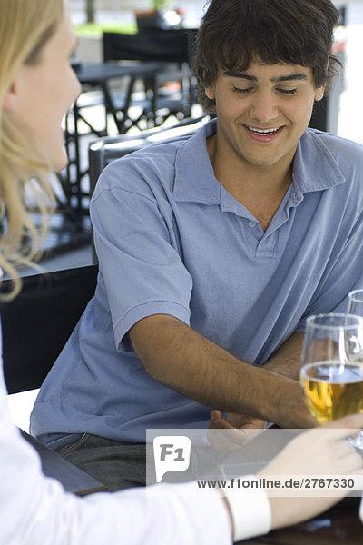 Junger Mann sitzend im Café mit Freund