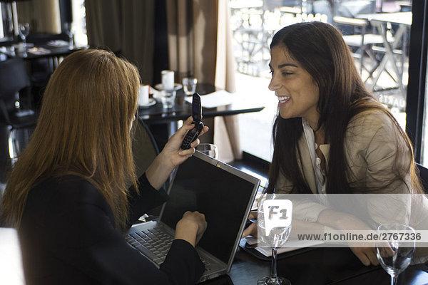 Zwei junge Frauen sitzen im Café  plaudern  eine mit Laptop und Handy