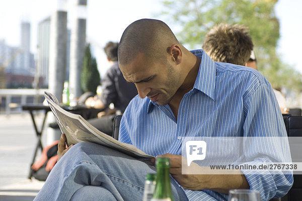 Mann sitzt auf dem Bürgersteig und liest Zeitung.