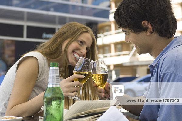 Junges Paar klirrende Biergläser im Freiluftcafé