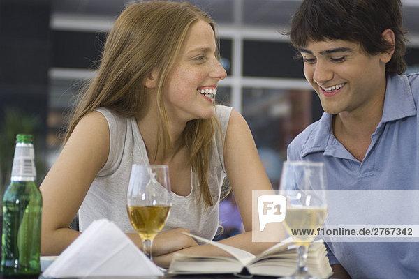 Junges Paar sitzt in einem Café im Freien und schaut sich gemeinsam das Buch an.
