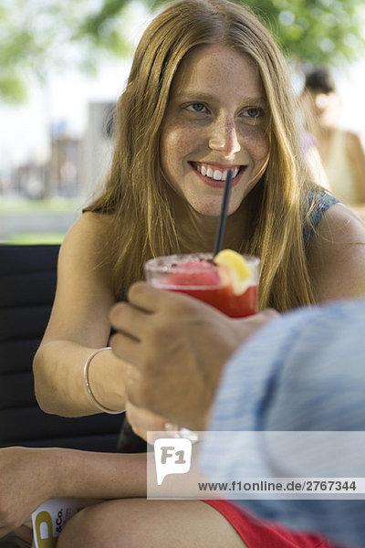 Junge Frau nimmt Cocktail von Freundin