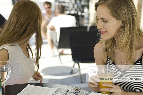 Frau sitzend im Café mit Freundin  Lesemagazin