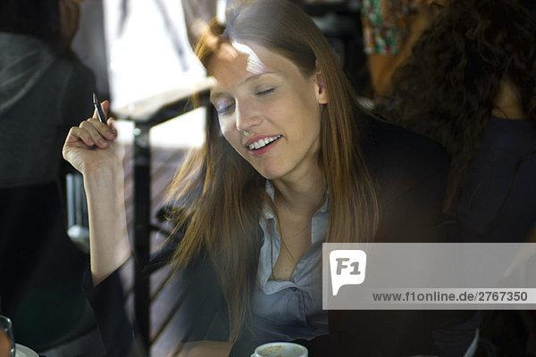 Frau im Café durchs Fenster gesehen mit Spiegelung