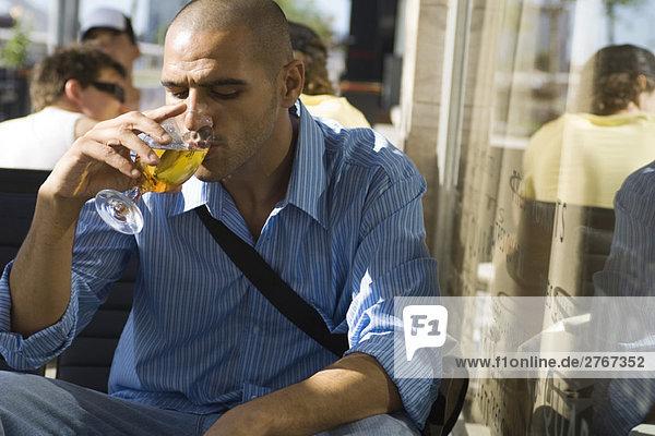Ein Mann trinkt ein Bier in einem Straßencafé.