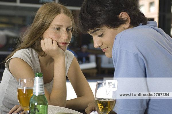 Junges Paar  das im Café sitzt und auf das Buch schaut.