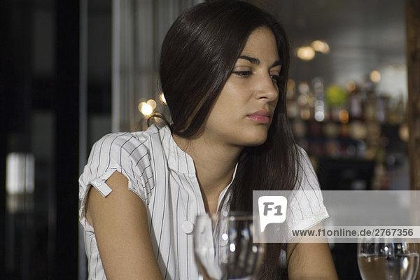 Frau sitzt im Restaurant und schaut weg.