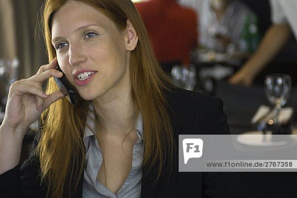 Junge Frau im Restaurant mit Handy