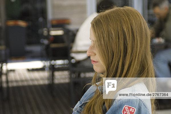 Junge Frau im Freien sitzend  Profil